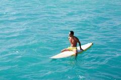 Męski surfingowiec patrzeje horyzont podczas gdy siedzący na jej surfboard Zdjęcie Stock