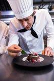 Męski szef kuchni garniruje deser z nowym liściem na kontuarze Zdjęcie Royalty Free