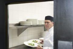 Męski szef kuchni Z jedzenie talerzami W kuchni Obrazy Royalty Free