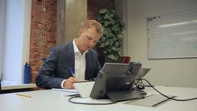 Męski szef pisze w notatniku podczas gdy siedzący w swój biurze zdjęcie wideo