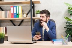 Męski szef pracuje z smartphone Brutalny biznesmen w biurze Doro?le? m??czyzna z brod? brodaty modni? u?ywa komputer obrazy stock