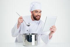 Męski szefa kuchni kucharz trzyma cyfrową pastylkę i przygotowywa jedzenie Obraz Stock