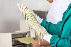 Męski szefa kuchni mienia spaghetti makaron Przy kuchnią Zdjęcie Stock