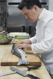 Męski szefa kuchni narządzania łosoś W kuchni obrazy royalty free
