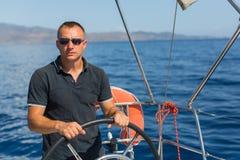 Męski szyper przy steru żeglowania łodzią, kontrola statek podczas dennej jacht rasy Fotografia Royalty Free