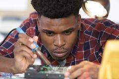 Męski technik używa lutowniczego żelazo na komputerowym narzędzia zdjęcia royalty free