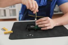 Męski technika naprawiania dysk twardy przy stołem zdjęcia royalty free