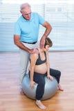 Męski terapeuta masowania kobieta w ciąży Zdjęcia Stock