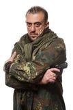 Męski terrorysta w militarnej kurtce z pistoletem wewnątrz Zdjęcia Royalty Free