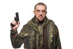 Męski terrorysta w militarnej kurtce z pistoletem wewnątrz Obraz Stock