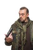 Męski terrorysta w militarnej kurtce z pistoletem wewnątrz Fotografia Royalty Free