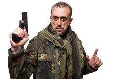 Męski terrorysta w militarnej kurtce z pistoletem wewnątrz Zdjęcie Stock