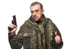 Męski terrorysta w militarnej kurtce z pistoletem wewnątrz Fotografia Stock