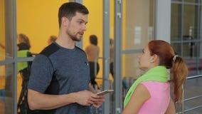 Męski trener komunikuje z kobietą w klubie sportowym indoors zbiory