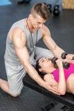 Męski trener pomaga kobiet podnośnych dumbbells Zdjęcia Stock