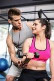 Męski trener pomaga kobiet podnośnych dumbbells Fotografia Royalty Free