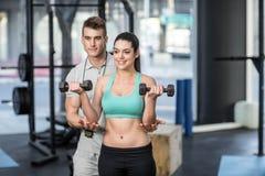 Męski trener pomaga kobiet podnośnych dumbbells Zdjęcie Royalty Free