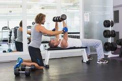 Męski trener pomaga młodego człowieka z dumbbells w gym Zdjęcia Stock