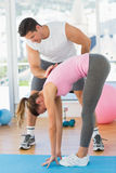 Męski trener pomaga młodej kobiety z Pilate ćwiczeniami Zdjęcia Royalty Free