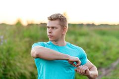 Męski trener robi rozgrzewce złącza Biegacz w ranku w parku Outdoors w parku Lato styl życia obrazy stock