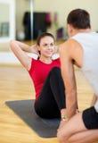 Męski trener z kobietą podnosi w gym robić siedzi Obraz Stock