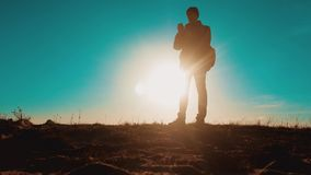 Męski turysta z psów stojakami na górze góry smartphone nawigacji mężczyzny sylwetka przy zmierzchem wycieczkowicz przygoda i zdjęcie wideo