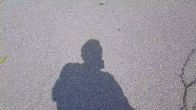 Męski turystyczny cień, więźniarski kryminalny odprowadzenie na asfaltowej drodze, patrzeje wokoło zdjęcie wideo