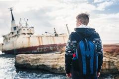 Męski turystyczny patrzejący zaniechanego statek na morza lub oceanu tylnym widoku Przygody i turystyki pojęcie Zdjęcie Stock