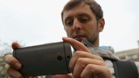 Męski turystyczny patrzeje zastosowanie z turystyczną marszrutą na jego smartphone zbiory