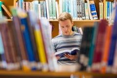 Męski uczeń czyta książkę w bibliotece Zdjęcia Stock