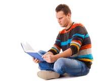 Męski uczeń czyta książkowego narządzanie dla egzaminu odizolowywającego Obrazy Royalty Free