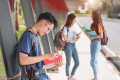 Męski uczeń czyta na kampusie Obraz Stock