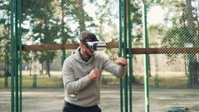 Męski uczeń jest ubranym rzeczywistość wirtualna szkła, boks samotną cieszy się aktywność i nowożytny trenuje w parku i zbiory
