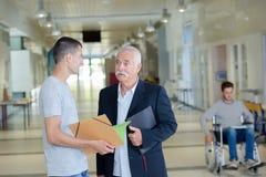 Męski uczeń szuka rada od nauczyciela Zdjęcia Stock