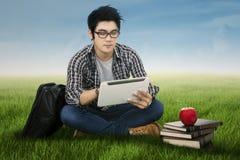 Męski uczeń używa cyfrową pastylkę outdoors Obraz Royalty Free