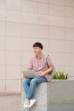 Męski uczeń używa laptop w szkoła wyższa kampusie Obrazy Stock
