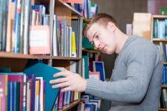 Męski uczeń wybiera książkę w bibliotece Zdjęcie Stock