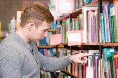 Męski uczeń wybiera książkę w bibliotece Fotografia Royalty Free
