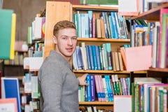 Męski uczeń wybiera książkę w bibliotece Obrazy Royalty Free
