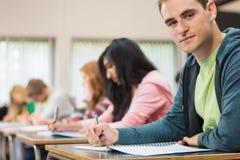 Męski uczeń z inny writing notatki w sala lekcyjnej Zdjęcie Royalty Free
