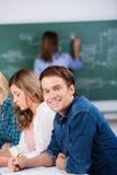 Męski uczeń Z kolega z klasy I nauczycielem Przy biurkiem Fotografia Stock