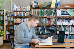 Męski uczeń z laptopu studiowaniem w bibliotece uniwersyteckiej Obrazy Royalty Free