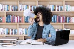 Męski uczeń z megafonem w bibliotece Obrazy Stock
