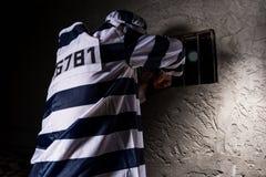 Męski więzień jest ubranym więzienie munduru próby uciekać przez Zdjęcia Royalty Free