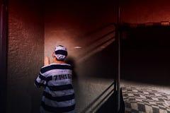 Męski więzień siedzi w kącie i ono modli się w więzieniu c Obrazy Royalty Free