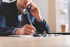 Męski writing przy stołem podczas gdy opowiadający na telefonie Fotografia Royalty Free