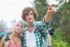 Męski wycieczkowicz pokazuje coś kobieta w lesie Obraz Royalty Free