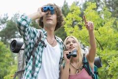 Męski wycieczkowicz używa lornetki podczas gdy dziewczyna pokazuje coś w lesie Zdjęcie Stock