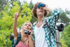 Męski wycieczkowicz używa lornetki podczas gdy dziewczyna pokazuje coś w lesie Zdjęcia Stock