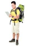Męski wycieczkowicz z plecakiem używać pastylka komputer Fotografia Stock